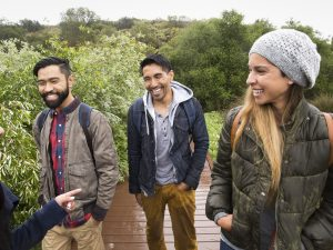 Smiling young woman and two young men walking in a park.