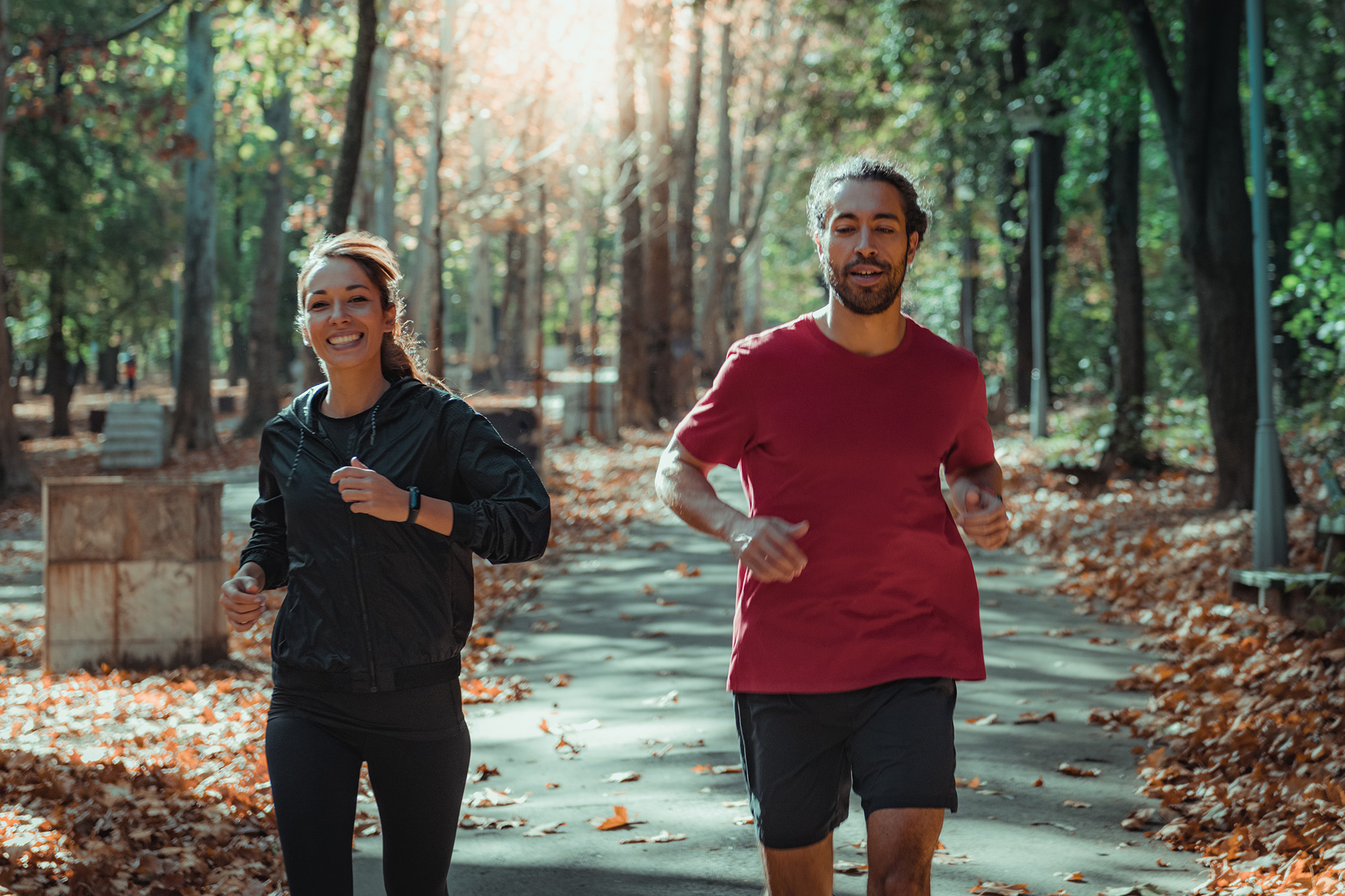 A man and woman, friends jogging together in Park